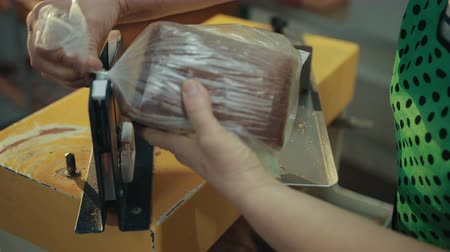 sarıcı : Female worker puts loaf of bread on metallic machine for wrapping with tape. Already sliced piece is wrapped in transparent plastic film by hands, not automatically.