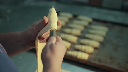 bafat : Confectioner woman hands are turning stainless steel tube, rolling dough around it. Female is making traditional French croissants in kitchen of bakehouse. Dostupné videozáznamy