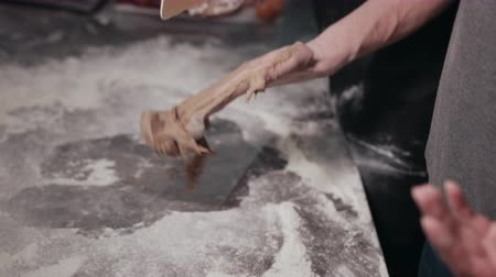 impastare : Process of scraping off elastic cocoa dough with plastic spatula from palms. White flour on stainless steel work table. Two people working together in kitchen making pastry.