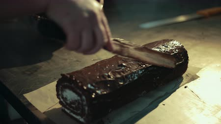 pergament : Hand with spatula is spreading chocolate on cocoa creamy swiss roll. Dessert lays on bakery parchment, stainless steel working table. Chef dabs soaked sponge cake, spreads melted chocolate evenly.