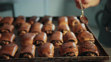 decorating : Buns with poppy seeds are decorated with dark melted chocolate from stainless steel spoon. Sweet baked rolls lay on oven-tray in rows in kitchen of bakery. Stock Footage