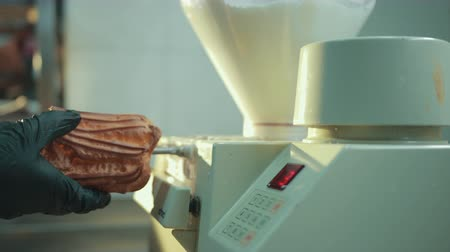 puffs : Automatic filling traditional French eclairs with whipped cream. Process of stuffing choux pastry, delicate mousse inside, using electric machine. Confectioner turns puffs to fill from both sides.
