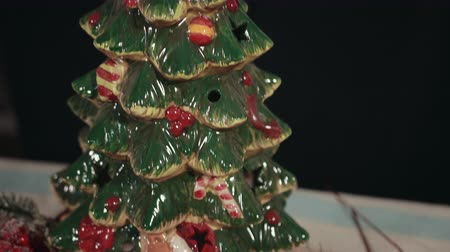 azevinho : Porcelain Christmas tree with painted baubles, traditional New Years Eve decorations. Mistletoe, branches of holly tree, red, white colors, snow on fir tree.