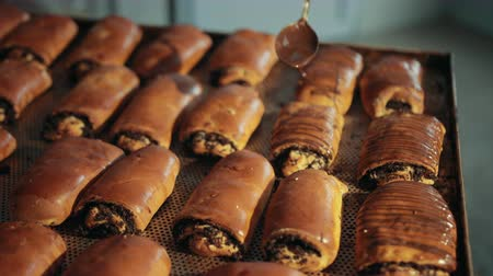 makowiec : Buns with poppy seeds are decorated with dark melted chocolate from stainless steel spoon. Sweet baked rolls lay on oven-tray in rows in kitchen of bakery. Wideo