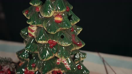 önemsiz şey : Porcelain Christmas tree with star, painted baubles, traditional New Years Eve decorations. Mistletoe, branches of holly tree, pine cones, red, white colors, snow on fir tree. Stok Video
