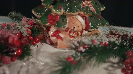 падуб : Ball, bear in hat and scarf painted on porcelain Christmas tree. Closeup of traditional New Years decorations, mistletoe, holly tree branches, snow.