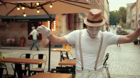 imaginární : Handsome young mime in hat, suspenders and white gloves is performing on street in white makeup. Entertainer is walking on straight thin line, looking down at it, balancing with half-raised arms. Dostupné videozáznamy