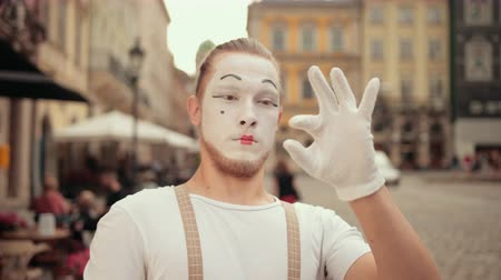 imaginário : Handsome young man is performing on street in white makeup. Mime in gloves pretends holding invisible thing between two fingers, then throws it away with another hand, looks surprised, smiles. Stock Footage