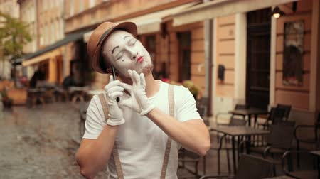 bretels : Young happy handsome performer of pantomime answers call, flirting, looking satisfied. Mime is smiling while talking, blowing kisses to mobile phone. Performance outdoors near street cafe. Stockvideo