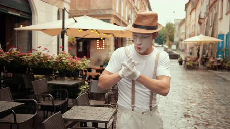 invisible : Young mime in hat, suspenders and white gloves performs on street near cafe. Entertainer looks confident, looking for something outside, searching. Then walks proudly with hands akimbo.