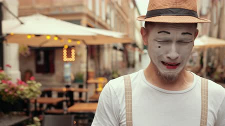kap : Entertainer in hat, suspenders, white makeup of mime gets upset, looks right, left with sad face. Facial expression shows emotionally hopeless mood. Performer is wiping tears with hand in white glove.
