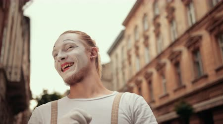 imaginární : Smiling young mime is performing on street in white makeup. Performer in gloves follows somebody with eyes, waving, moving arms, winking, then angry with his hand. Facial expressions change quickly.