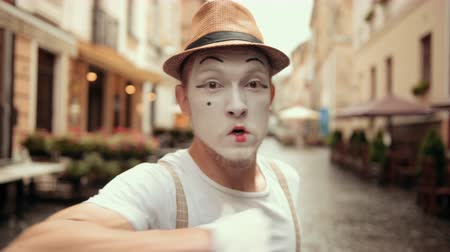 invisible : Young mime beckons to fight, punches right into camera on street near cafe. Entertainer in hat, suspenders, walks looking bully. Artist with bold, cocky look, angry facial expression is moving fists.