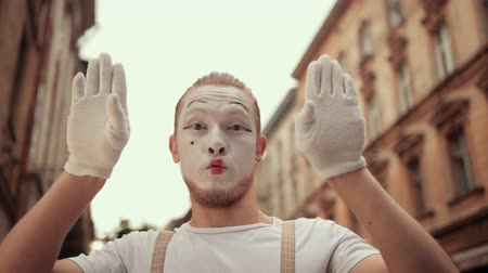 imaginární : Handsome young mime is performing on street in special makeup. Performer in white gloves plays with camera, hiding behind hands, moving head to sides, down, looking satisfied, surprised, nodding.