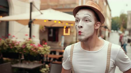 imaginário : Young mime is arguing, swearing, reviling with somebody on street near cafe. Performing by entertainer in hat, suspenders, makeup. Artist with raised eyebrows, angry facial expression is moving arms.