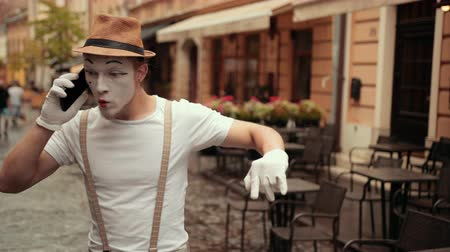актер : Young mime is talking on phone, explaining something. Performer is getting angry, starts shouting while conversation. Then entertainer is taking off his hat.