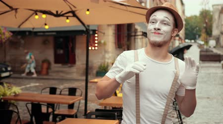 yüz buruşturma : Young entertainer is performing on street in makeup. Performer is looking left, right interested, surprised. Mime in white gloves greets people, smiling, holding suspenders, then turns around.