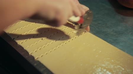 segmento : Baker is using pastry wheel for cutting dough into pieces. Female cook works with raw pastry, separating it by rolling knife that makes curved edges.