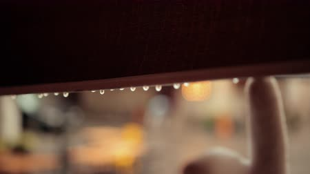 markiza : Raindrops dripping from edge of cafe canopy. Droplets are falling down after rain. Then hand in glove is wiping water with finger. Shot from shelter, view on street, blurred background. Wideo
