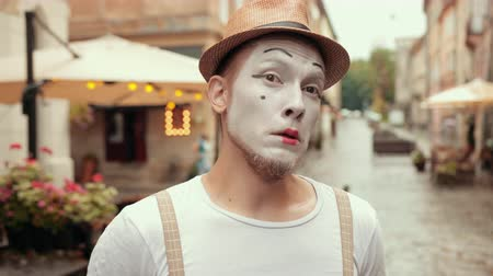 invisible : Entertainer in hat, suspenders, white makeup of mime gets upset, looks up with sad face. Facial expression shows emotionally hopeless mood. Then performer is scared, surprised. Stock Footage