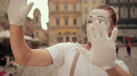 comediante : Handsome young mime with fair hair, beard is performing on street in gloves, special white makeup. Artist looks up, dissatisfied as something invisible falls, then pushes it back with effort.