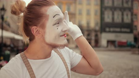 utánzás : Smiling young mime is performing on street in white makeup. Performer in gloves follows somebody with eyes, waving, moving hands, arms, blowing kiss, winking. Facial expressions change quickly.