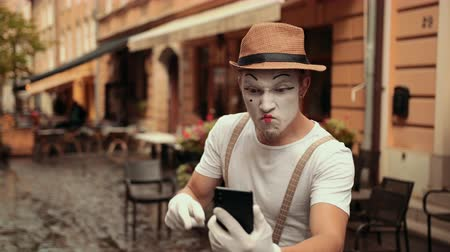 significar : Young handsome mime looks at phone, surprised, disoriented. Hits head, becoming normal. Then points at cellphone, shouting, arguing. Street performance near cafe. Stock Footage