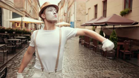 imaginární : Young mime beckons somebody to fight on street near cafe. Entertainer in hat, suspenders, makeup, walks looking bully. Artist with bold, cocky look, angry facial expression is moving arms, fists.