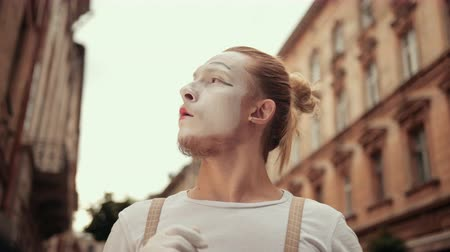 гримаса : Young mime is performing on street in white makeup. His facial expressions change quickly, first interested, then perplexed, baffled, puzzled, surprised.