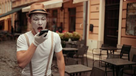 imaginární : Handsome young mime with bored facial expression rolls eyes talking on phone. Performer holding cellphone near ear, then on palm, calling. Entertainer is shouting, arguing while conversation, happy.