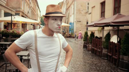 imaginární : Young handsome mime in hat, suspenders and white gloves performs on street near cafe. Entertainer looks confident, looking for something outside, searching. Then walks proudly with hands akimbo. Dostupné videozáznamy