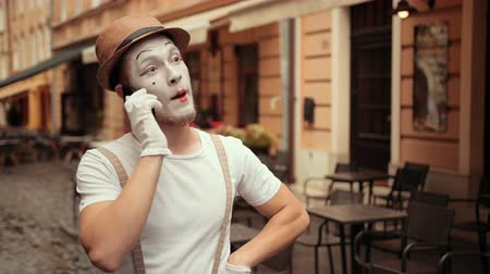 gururlu : Young happy handsome performer of pantomime answers call, flirting, looking satisfied. Mime is smiling while talking, listening attentively with dreaming face. Performance outdoors near street cafe. Stok Video