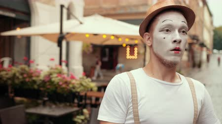 invisible : Young handsome mime is performing on street near cafe, denies, says no certainly. Performing by entertainer in hat, suspenders, makeup. Artist is moving arms, looks scared.