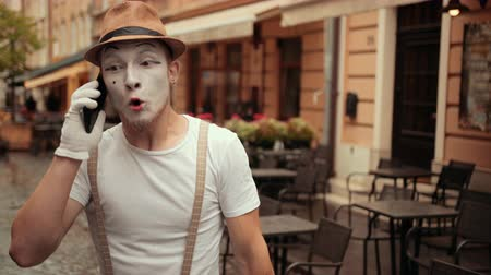 invisible : Handsome young mime is talking on phone. Performer holding cellphone near ear, then on palm, calling. Entertainer is shouting, arguing, then wants to crash device but pets it instead. Stock Footage