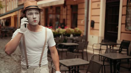 invisible : Handsome young mime with angry facial expression calls on his phone. Performer holding cellphone near ear, calling. Entertainer is shouting, arguing while conversation.