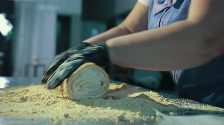 покрытый : Female baker is covering top, sides of swiss roll with chopped nuts. Then woman takes parchment, puts on cake, continues rolling on stainless steel work table.