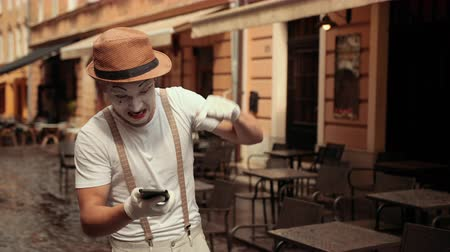 médio : Handsome young mime with dissatisfied facial expression is shouting at his phone. Performer points at screen of cellphone several times, standing on street near cafe.
