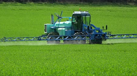 Agriculture fertilizer working on farming field, agriculture machinery working on cultivated field and spraying pesticide