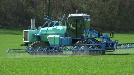 spraying : Agriculture fertilizer working on farming field, agriculture machinery working on cultivated field and spraying pesticide
