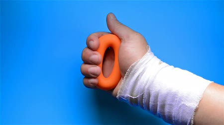 squeeze : a hurt hand doing rehabilitation exercises by squeezing a hand grip ring
