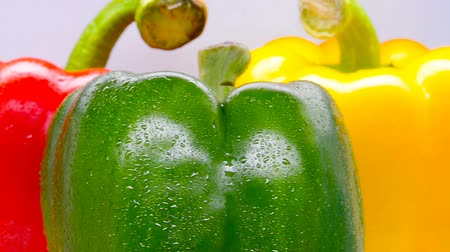 celý : fresh red green and yellow bell peppers with drips rotating