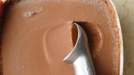 smetanový : slow motion of digging out a chocolate flavor ice cream ball