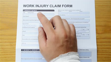 compensar : man with a wrap hand reading a work injury claim form