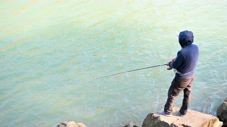 szczupak : man standing and fishing on the edge of a river Wideo