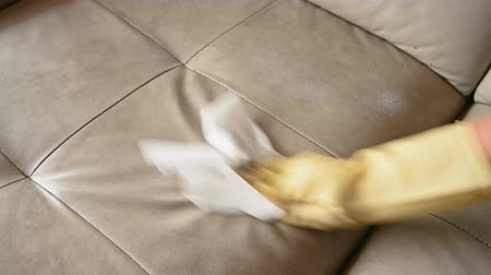 dezenfekte etmek : man cleaning a leather sofa with chemical foam Stok Video