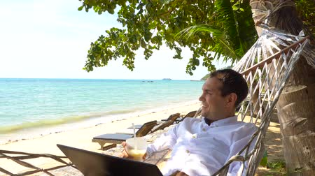 hamak : Young man work on laptop relaxing in hammock with seaview Dostupné videozáznamy