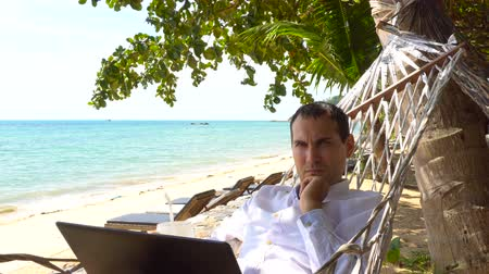 homály : Serious man work on laptop relaxing in hammock with seaview