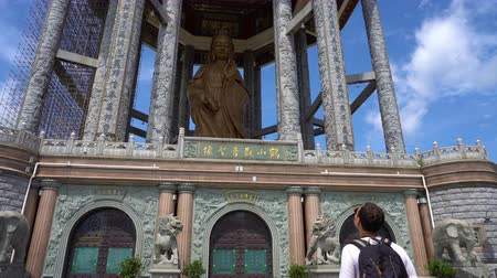 religia : Young caucasian man looking at Guan Yin statue