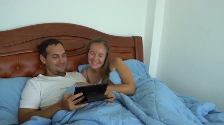 Romantic couple watch tablet together and laugh in bed