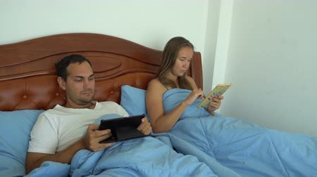 Young couple using their tablets in bed ignoring each other. Family issues